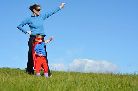 divertirsi: Madre Superhero e figlia contro sfondo drammatico cielo blu con copia spazio. concetto di fotografia di Super eroe, Power Girl, il gioco finta, l'infanzia, l'immaginazione.