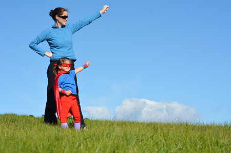 pretending: Superhero mother and daughter against dramatic blue sky background with copy space. concept photo of Super hero, girl power, play pretend, childhood, imagination. Stock Photo