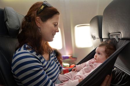 母は、飛行中に彼女の幼児の赤ん坊を運ぶ。赤ちゃんと一緒に空の旅のコンセプト写真。
