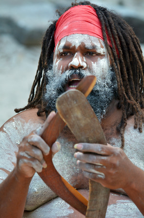 Portrait of one Yugambeh Aboriginal man holds boomerangs and sing during Aboriginal culture show in Queensland, Australia. photo
