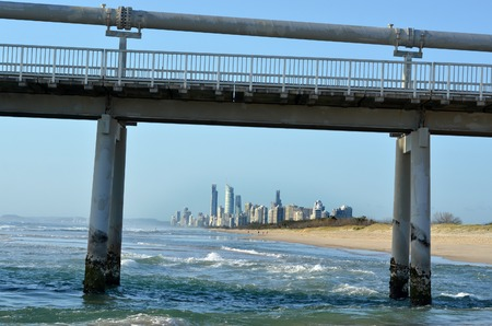 surfers paradise: Gold Coast Pier at the Spit Queensland Australia Sunrise over the Gold Coast Pier at the Spit while Surfers Paradise skyline is in the background in Queensland Australia. Stock Photo