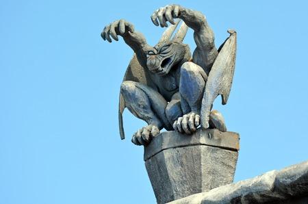 Waterspuwer daemon zitten op een dak van een gebouw. Stockfoto