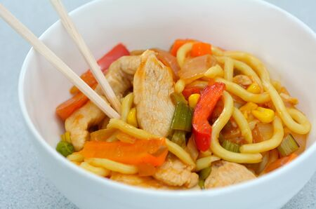 bawl: Asian noodles dish Asian noodles dish of chicken and vegetables served in a bawl and chopsticks.