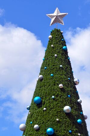 merry chrismas: Christmas Tree Christmas Tree against with a star against blue sky with white clouds outdoor. Holiday concept.