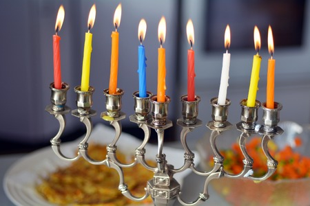 Hanukkah menorah lit with eight candles during dinner celebration at the last day of Hanukah. Stock Photo