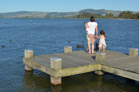 age 5: Mother with two children (girls age 5 and baby 01) stand on a jetty and looks at Black swans on Lake Rotorua waterfront, New Zealand. Stock Photo