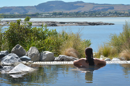 Young woman having a spa in outdoors hot pool in Rotorua, New Zealand. Stock Photo