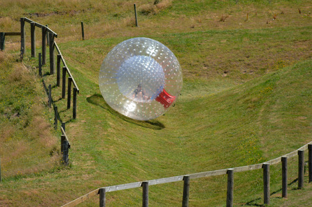 slopes: Man rides in ball rolling Zorbing in Rotorua, New Zealand. Stock Photo