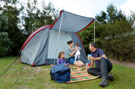 camping equipment: Young family, father and mother with two children camping in a tent outdoors.