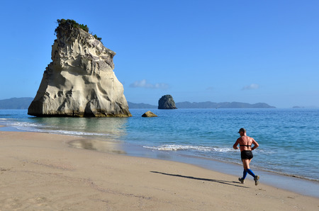visitors area: WHITIANGA, NZL - Jan 20 2015: Man runs on the beach of Cathedral Cove.The area is very popular with tourists, and receives around 150,000 visitors per year.