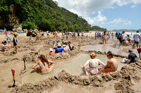 new zealand: WHITIANGA, NZL - Jan 20 2015:Visitors making small hot water pools in Hot Water beach.it one of the most popular geothermal attractions in New Zealand, about 700,000 people visit the beach annually. Editorial