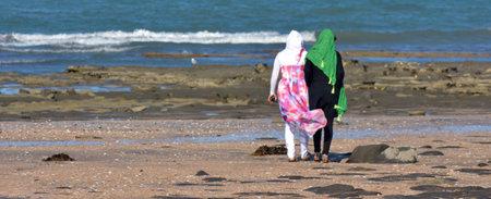 femmes muslim: AUCKLAND, NZL - 25 janvier 2015: Deux femmes musulmanes sur la mutilation g�nitale f�minine beach.Over 130 millions de femmes et de filles ont connu, 21% des filles et des femmes musulmanes ont subi une MGF.