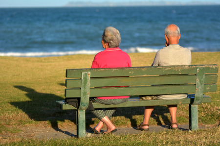 65 years old: AUCKLAND, NZL - JAN 2015:Two old retired couple sit on a bench.By 2051, there will be over 1.14 million people aged 65 years and over in New Zealand.