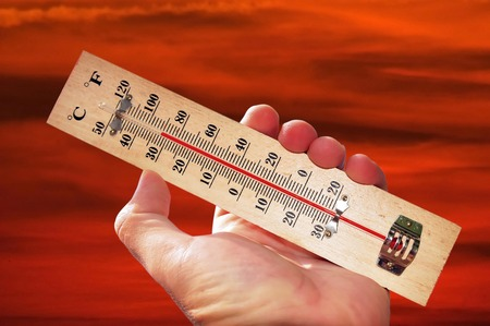 high scale: A hand and temperature scale over a red sky shows high temperatures during a heat wave.