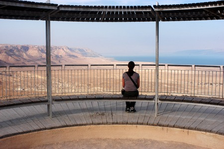 Tourist looks at the landscape of the Dead sea valley from Masada Fortress, Israel
