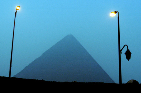 khufu: The Pyramid of Khufu, viewed through the smog, minutes before sunrise  at the great pyramids in Giza, Egypt.