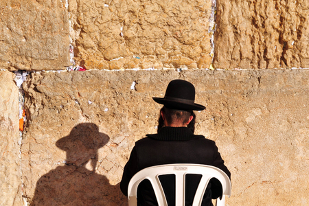 siddur: A  Jewish orthodox man prays at the Western Wall in the old city of Jerusalem Israel