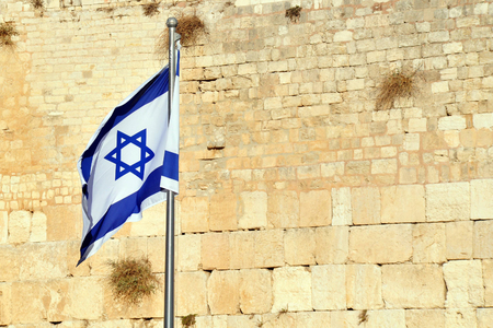 The Israeli National Flag against the Kotel Wailing Western Wall on November 12 2008 in Jerusalem Israel.It is a remnant of the ancient wall that surrounded the Jewish Temples and is the most sacred site recognized by the Jewish faith outside of the Temp Stock Photo