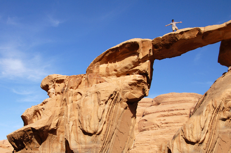 rock arch: Visitor on top of a natural rock arch in Wadi Rum, Jordan.