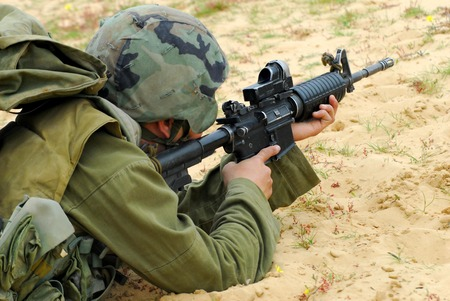 An Israeli defense forces soldier dressed in uniform aims his M16 rifle while on duty 報道画像