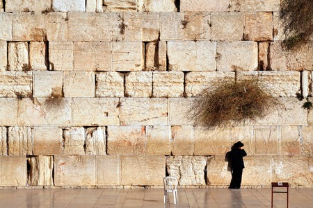 Jewish man is praying at the western wall in the old city in Jerusalem Israel