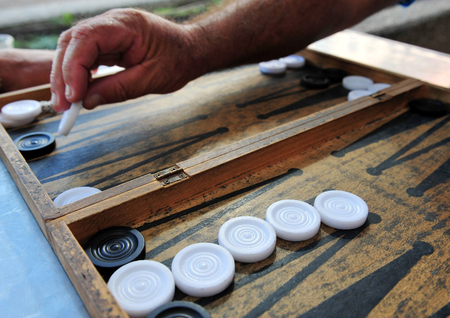 Close up of players hand palys Backgammon game. photo