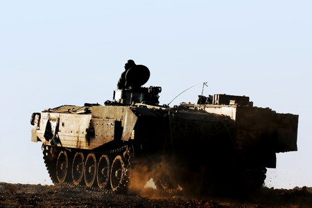 Silhouette of an army soldier on a moving heavily armored personnel carrier. photo