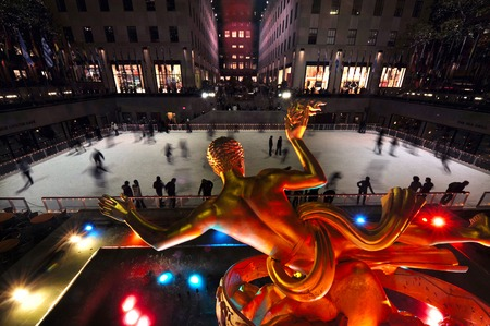 People ice skate at the famous ice arena of Rockefeller Center during winter time in Manhattan New York USA