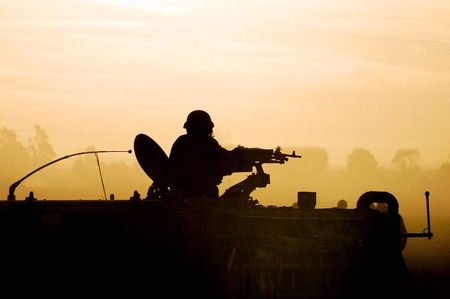 Silhouette of an army soldier preparing his tank and weapons at sunset
