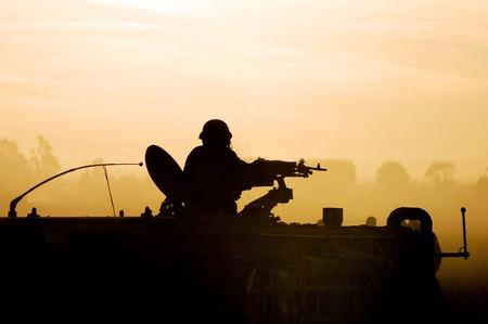 wojenne: Sylwetka żołnierza armii przygotowuje swój zbiornik i broni na zachodzie słońca