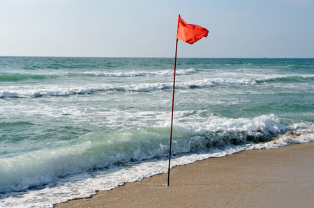 no swimming: A warning Red flag of danger at sea and no swimming mark posted at the beach.