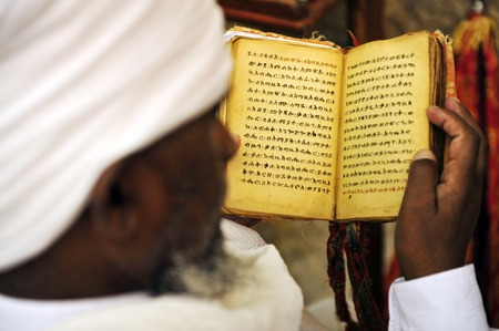 kippah: An Israeli Jewish orthodox Ethiopian man prays in a synagogue reads a torah book siddur and wears tefillin tzitzit and tallit