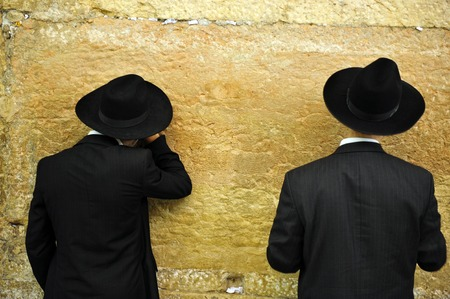Jewish Men are praying at the western wall in the old city in Jerusalem Israel