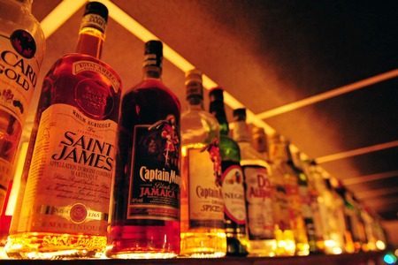 jovenes tomando alcohol: Botellas de alcohol en un bar. Editorial