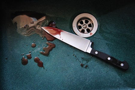 blade cut: A knife with drops of blood on it resting in a dark green sink