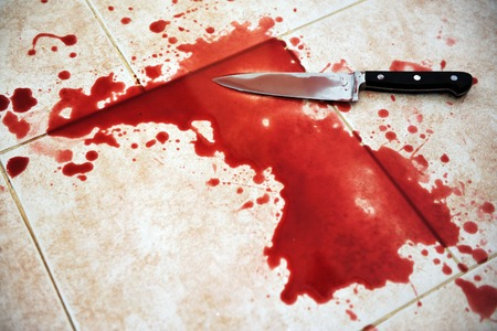 die cut: Conceptual image of a sharp knife with blood on it resting on tiles on the floor Stock Photo