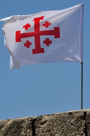 "holy land: A Crusader flag of Jerusalem at Mount Tabor, Israel. The cross of the Holy Land, a Greek cross in red on a white background, also known as the ""Jerusalem cross"", is the symbol of the Custody of the Holy Land."