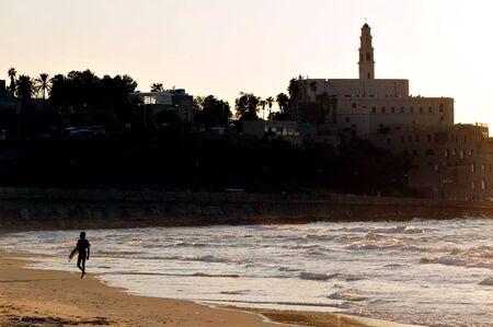 jaffa: Wave surfer against Jaffa skyline during sunset in Tel Aviv Jaffa port Israel