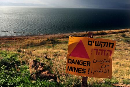 A sign reads: Danger Mines against the Sea of Galilee lake Kinneret on the side of Golan heights, Israel. photo