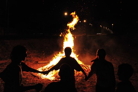 Children are holding hands and dancing in a circle around a bonfire. Archivio Fotografico