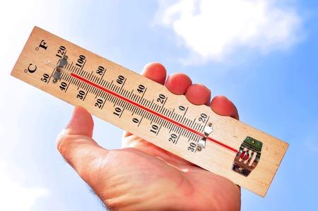 手と温度スケールは熱波の間に 41 の摂氏温度を示しています 写真素材