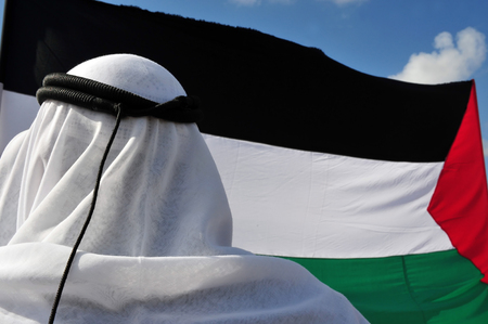iqal: A Palestinian man is wearing a traditional keffiyeh or ghutra (white) and iqal (black) with the Palestinian flag in the background Stock Photo
