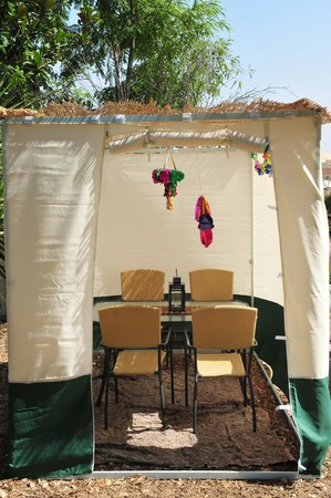 tabernacles: A sukkah with table, chairs and decorations. A sukkah is a temporary hut constructed for use during the week-long Jewish festival of Sukkot. It is topped with branches and often well decorated with autumnal, harvest or Judaic themes. Stock Photo