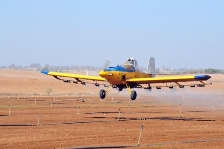 A spray plane or crop duster applies chemicals to a field of crops. Stock Photo
