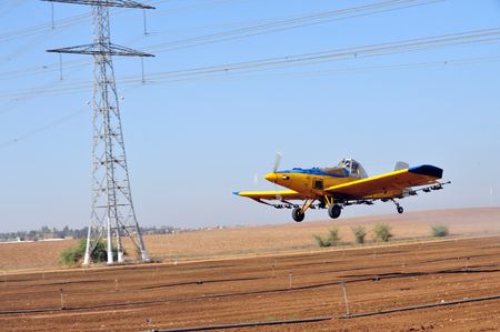 dangerously: A spray plane or crop duster flies dangerously underneath electricity power lines while applying chemicals to a field of crops.