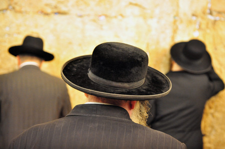 Jewish Men are praying at the western wall in the old city in Jerusalem, Israel. photo