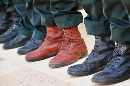 An army soldier wears brown boots while all other soldiers wear traditional black boots while participating in a military parade Stock Photo