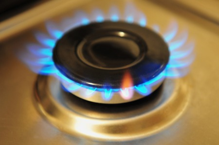 gas stove: Stainless steel gas burner turned on with blue gas flame.