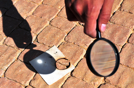 Lighting a fire with a magnifying glass Imagens