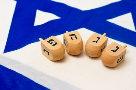 hebrew alphabet: A white and blue Israeli Flag with the star of david on it with wooden dreidels for the Jewish holiday of Hanukkah.